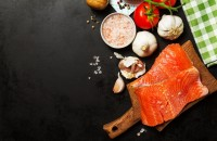 Tasty colorful Food Background with fresh Raw Fish Salmon and Cooking Ingredients - Olive Oil, Salt, Tomatoes, Spaghetti and Spices on Old Metal Tray. Top View. Cooking, Healthy Food Concept.